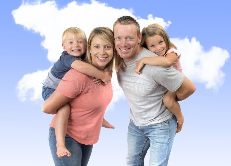 Jonge gelukkige en mooie Amerikaanse familie met echtgenoot en vrouw die hun rug dragen weinig zoon en mooie jonge dochter isolat stock foto's