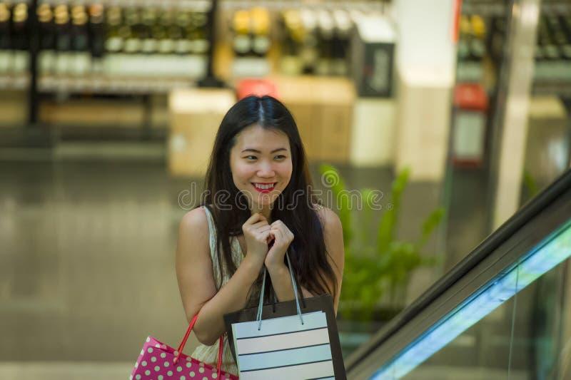 Jonge gelukkige en mooie Aziatische Koreaanse vrouw bij wandelgalerijroltrap dragende het winkelen zakken in wandelgalerij kopen  stock fotografie