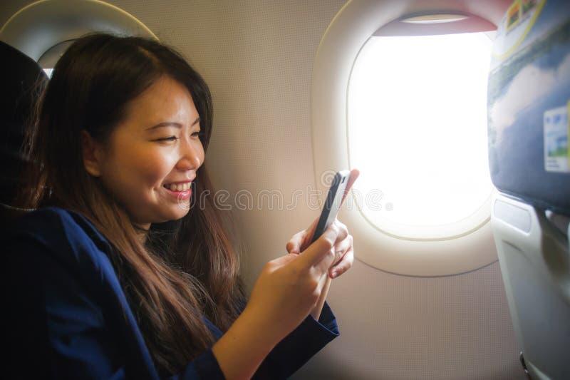 Jonge gelukkige en mooie Aziatische Koreaanse vrouw die voor zaken binnen vliegtuigcabine reizen die vrolijke gebruikende mobiele stock foto