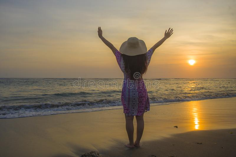Jonge gelukkige en ontspannen vrouw die in de Zomerhoed de zon over het overzees tijdens een verbazende mooie zonsondergang bij t royalty-vrije stock foto