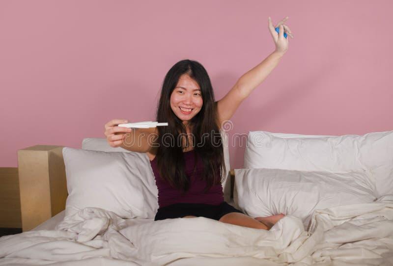 Jonge gelukkige en opgewekte Aziatische Koreaanse vrouw die in de zwangerschapstest van de bedholding verraste positieve zwangere royalty-vrije stock afbeelding