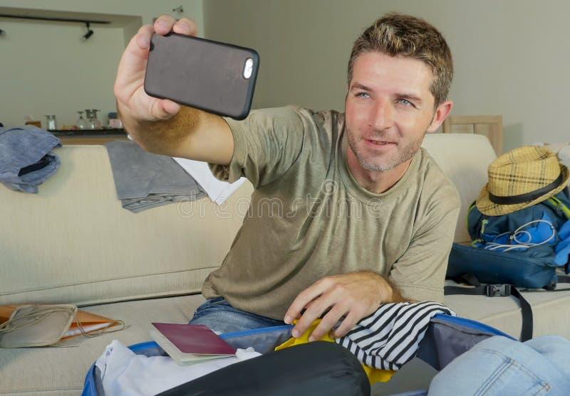 Jonge gelukkige en opgewekte mens die selfie portret met mobiele telefooncamera nemen terwijl de inpakkende reiskoffer en het voo royalty-vrije stock foto