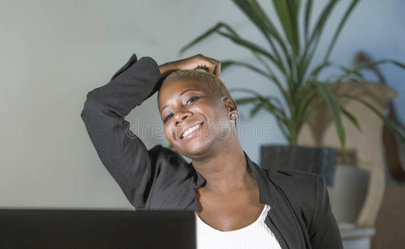 Jonge gelukkige en succesvolle zwarte afro Amerikaanse vrouw die bij bureaustoel leunen die en het blije werken bij laptop comput stock fotografie