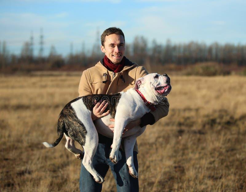 Jonge gelukkige Europees glimlachende en lachende holding in handen een ras van de hond Engels buldog royalty-vrije stock afbeelding