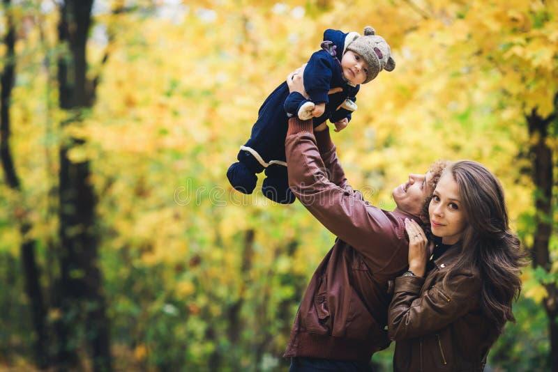 Jonge gelukkige familie in de herfst in park De vader werpt omhoog vreugdevol zijn zoon royalty-vrije stock foto's