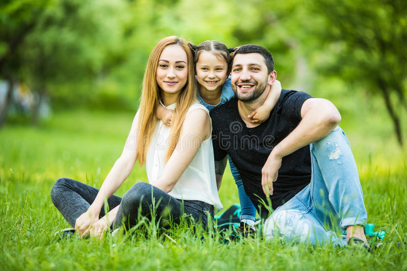 Jonge gelukkige familie in de zomerpark De vader en de moeder brengen tijd in de zomerpark met door hun dochter stock fotografie