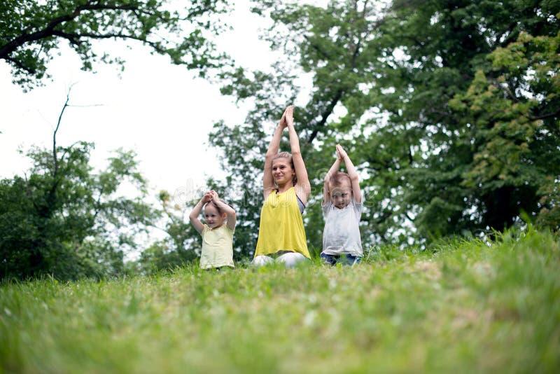 Jonge gelukkige familie die de oefeningen van de Yogaontspanning op een gras doen stock afbeeldingen