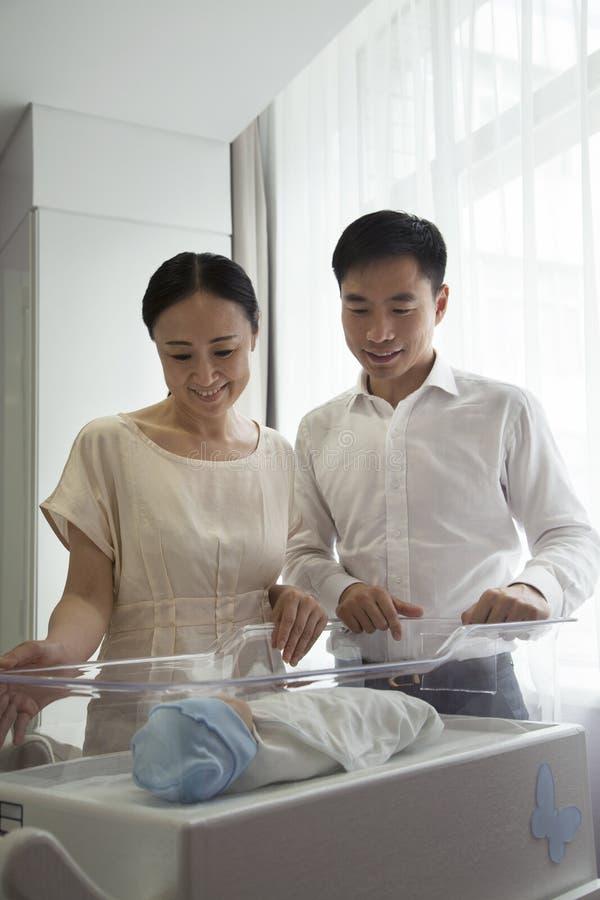 Jonge gelukkige familie die neer hun pasgeboren in het het ziekenhuiskinderdagverblijf bekijken stock fotografie