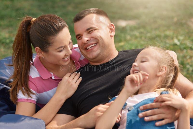 Jonge gelukkige familie het besteden vrije tijd in park op picknick, moeder en vaderlach van de grap van doughter, zich terloops  stock fotografie