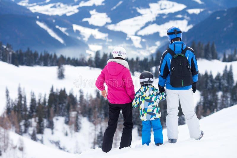 Jonge gelukkige familie met één kind, die in de bergen ski?en stock fotografie