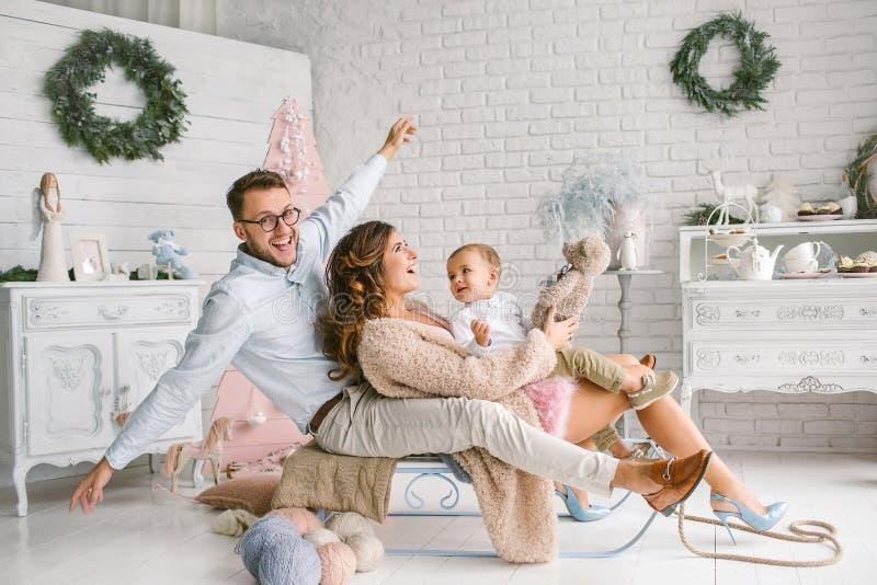 Jonge gelukkige familie met baby in de studio van het Kerstmisdecor stock fotografie