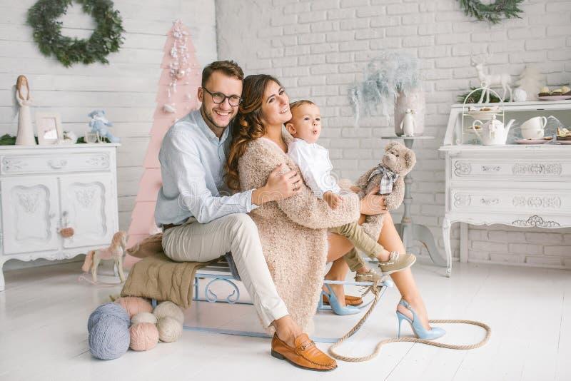 Jonge gelukkige familie met baby in de studio van het Kerstmisdecor stock afbeeldingen