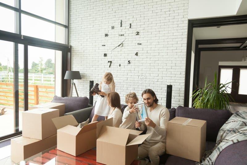 Jonge gelukkige familie met jonge geitjes die dozen in woonkamer uitpakken stock afbeeldingen