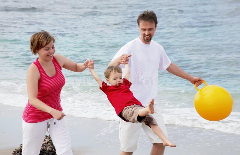 Jonge gelukkige familie op het strand stock afbeelding