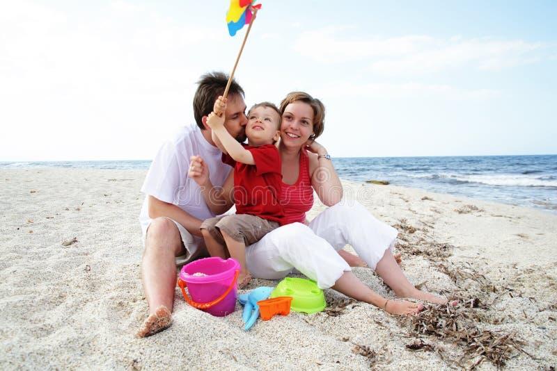 Jonge gelukkige familie op het strand royalty-vrije stock afbeelding