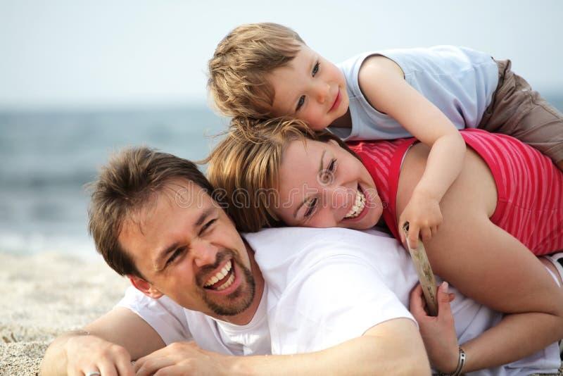 Jonge gelukkige familie op het strand royalty-vrije stock foto