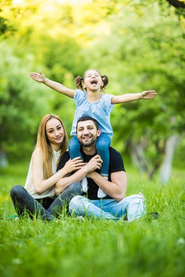 Jonge gelukkige familie van drie die pret hebben samen openlucht Mooi heeft weinig dochter die op haar vadervervoer per kangoeroe stock afbeelding
