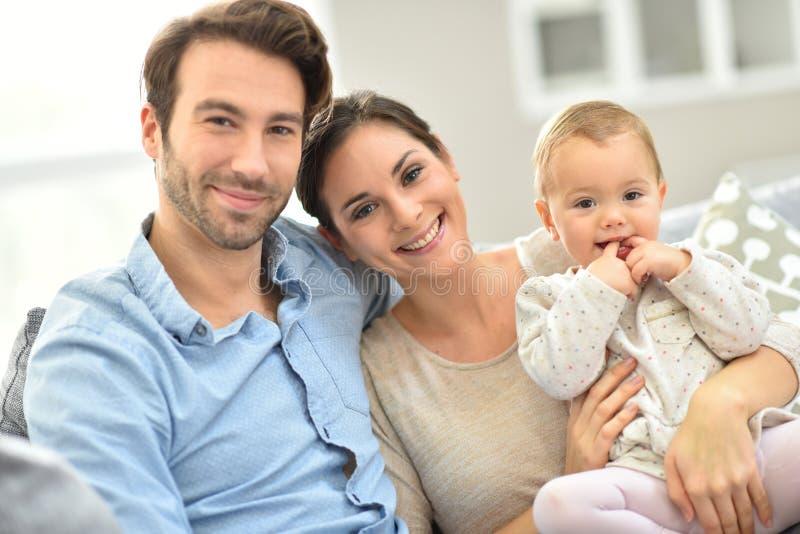 Jonge gelukkige familie van drie op bank stock foto