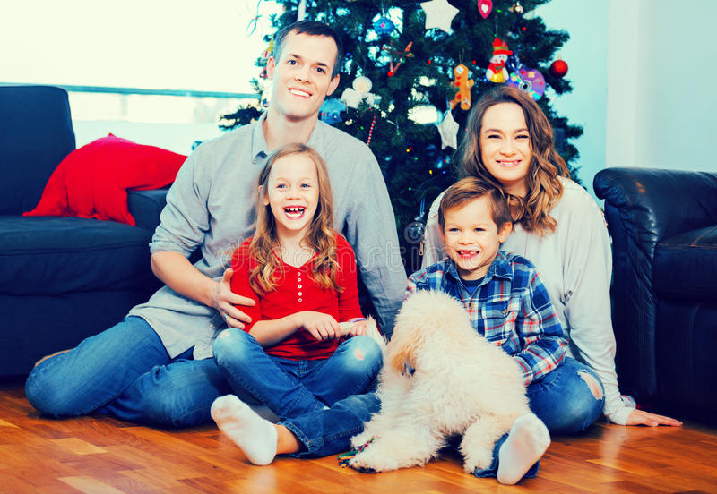 Jonge gelukkige familiezitting door Kerstboom thuis stock fotografie