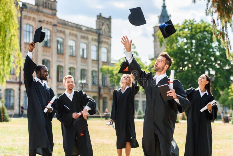 jonge gelukkige gediplomeerde studenten die op graduatiekappen werpen royalty-vrije stock foto