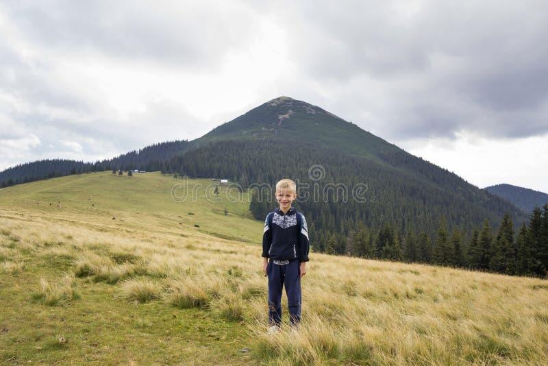 Jonge gelukkige glimlachende kindjongen met rugzak die zich in berg grasrijke vallei bevinden op achtergrond van de zomerlandscha stock foto's