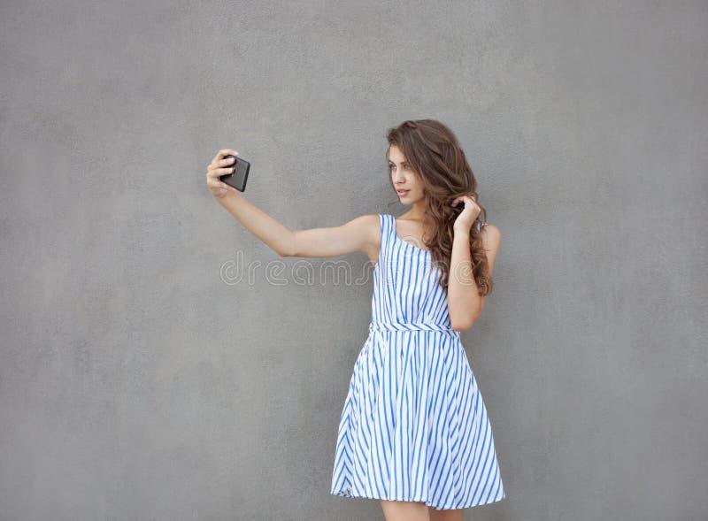 Jonge gelukkige glimlachende mooie vrouw in lichte kleding met het lange donkerbruine krullende haar stellen tegen muur op warm stock foto