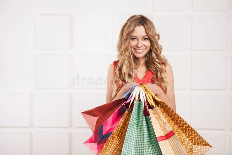 jonge gelukkige glimlachende vrouw met het winkelen zakken stock afbeelding