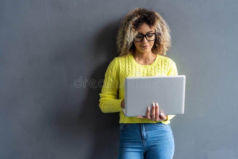 Jonge gelukkige glimlachende vrouw in vrijetijdskleding die laptop houden en e-mail verzenden naar haar beste vriend stock foto's