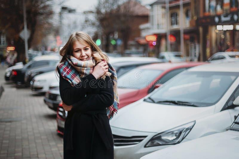 Jonge gelukkige glimlachende vrouw in zwarte laag en sjaal die rond stad lopen Het wachten op haar vriend Het wachten op vergader stock afbeelding