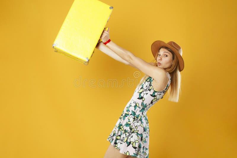 Jonge gelukkige grappige vrouw die gele koffer over oranje rug houden royalty-vrije stock foto