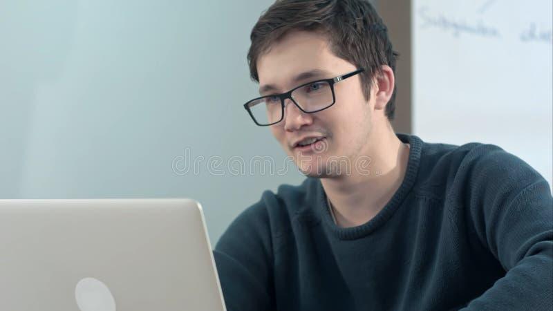 Jonge gelukkige het glimlachen kerel die laptop voor videogesprek in school met behulp van royalty-vrije stock afbeelding