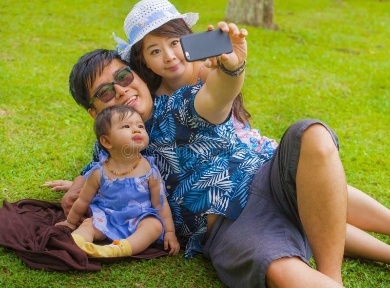 Jonge gelukkige houdende van Aziatische Chinese familie met ouders en zoete babydochter bij stadspark samen met vader die selfie  stock afbeelding