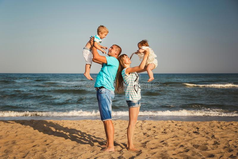 Jonge gelukkige houdende van familie met kleine jonge geitjes die pret hebben bij strand samen dichtbij het oceaan, gelukkige con stock fotografie