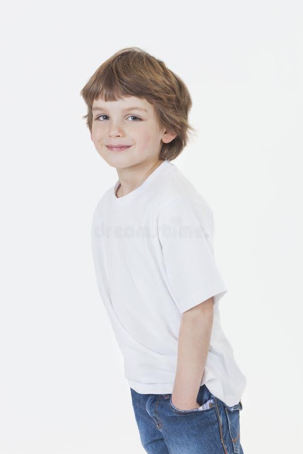 Jonge Gelukkige Jongen die in Jeans en T-shirt glimlachen stock afbeelding