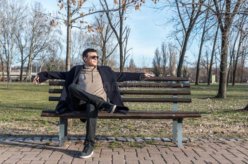 Jonge gelukkige kerel met zonnebril en glimlachzitting op de bank in het park die van het leven en van de zonnige dag genieten royalty-vrije stock afbeelding