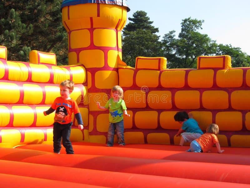 Jonge gelukkige kinderen die op een bouncykasteel spelen. stock afbeeldingen