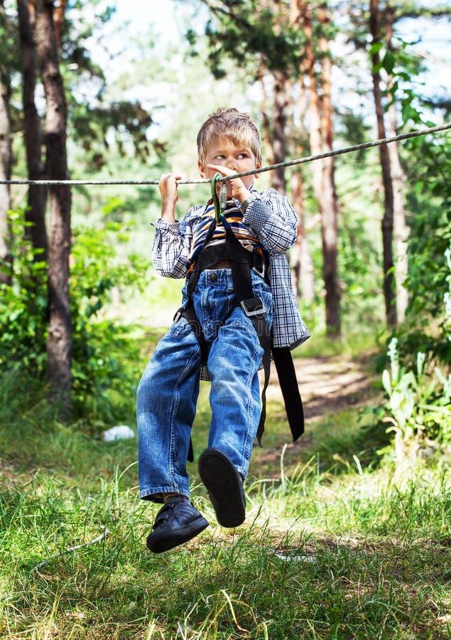 Jonge gelukkige kindjongen in avonturenpark stock foto's