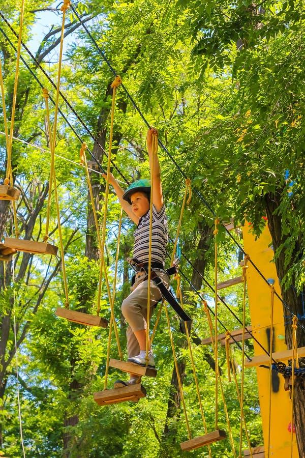 Jonge gelukkige kindjongen in avonturenpark in veiligheidsmateriaal royalty-vrije stock afbeelding