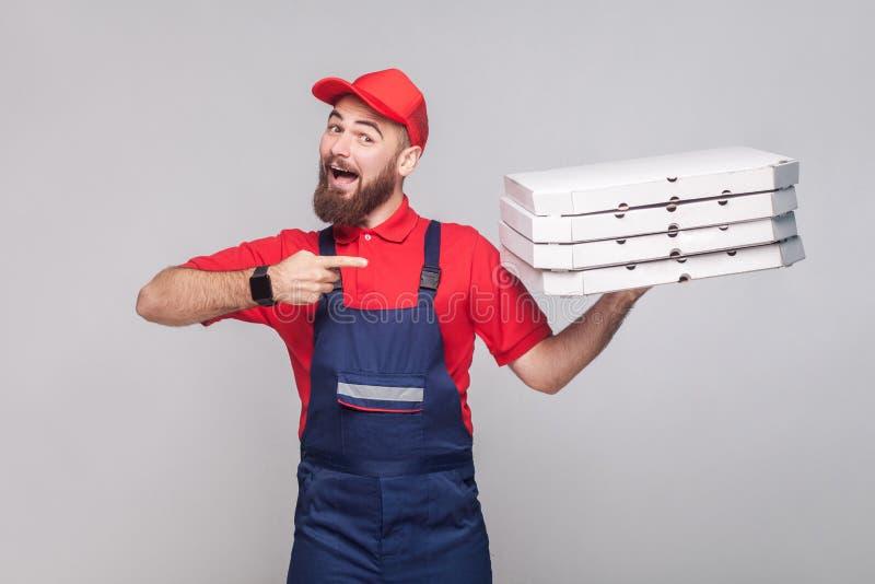 Jonge gelukkige leveringsmens met baard in blauwe eenvormige en rode t-sh stock afbeelding
