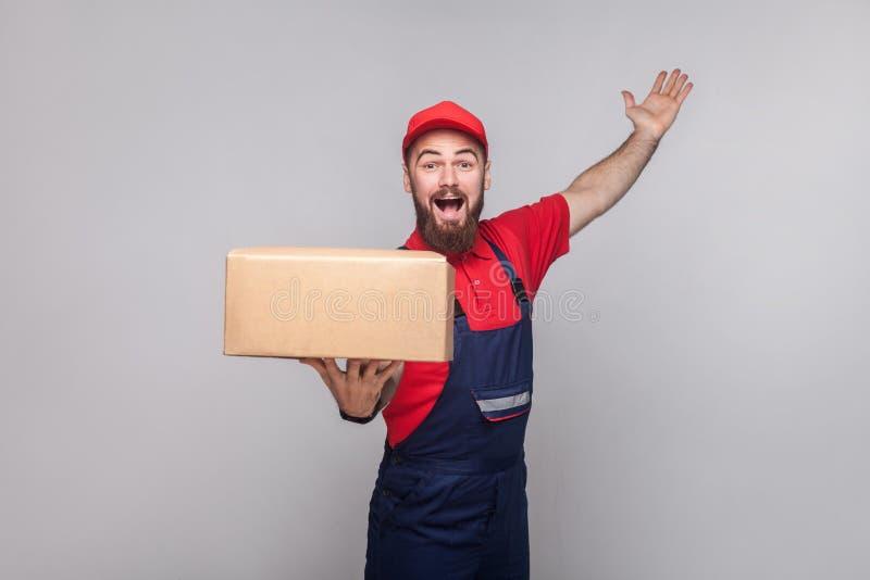 Jonge gelukkige logistische leveringsmens met baard in blauwe eenvormig en stock afbeelding