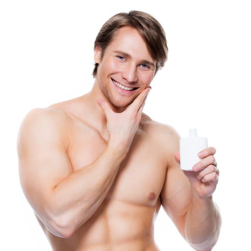 Jonge gelukkige mens die lotion op gezicht toepassen stock foto's