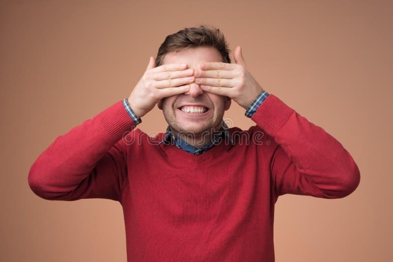 Jonge gelukkige mens die ogen behandelen met handen royalty-vrije stock foto