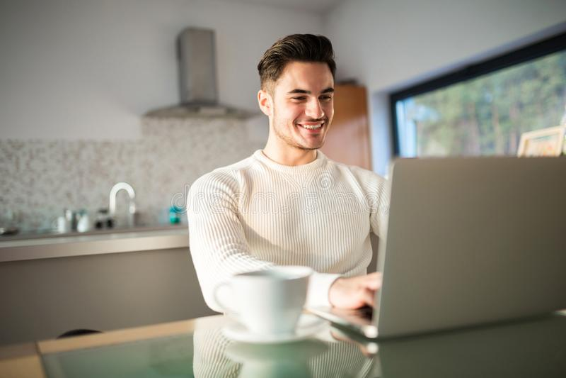 Jonge gelukkige mens die thuis aan laptop werken stock fotografie