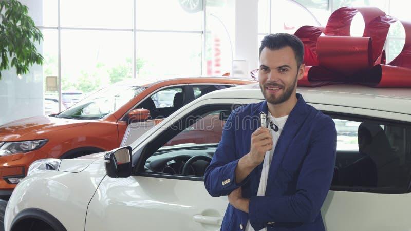 Jonge gelukkige mens die tonend autosleutels aan zijn nieuwe auto glimlachen stock afbeelding