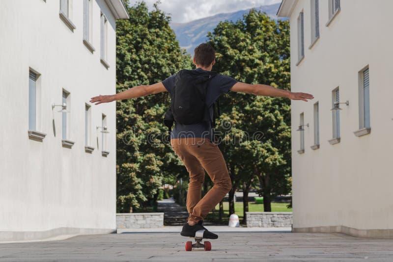 Jonge gelukkige mens met rugzak die longboard voor het gaan naar school na de zomervakantie gebruiken stock foto