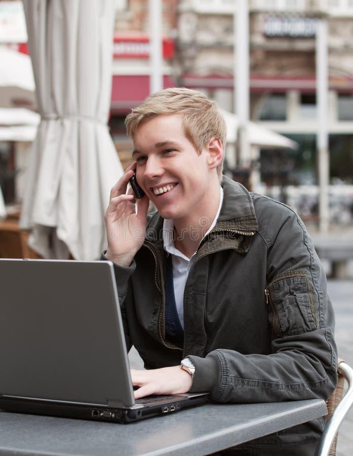 Jonge gelukkige mens met telefoon en laptop royalty-vrije stock afbeeldingen