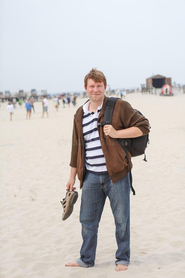 Jonge gelukkige mens op het strand van St. Peter Ording, Noordzee, royalty-vrije stock afbeeldingen