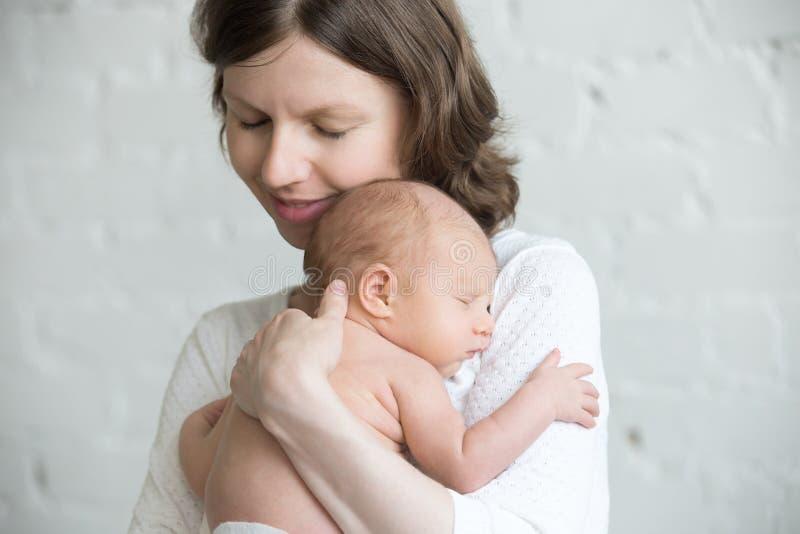 Jonge gelukkige moeder die teder haar pasgeboren baby koesteren stock foto's
