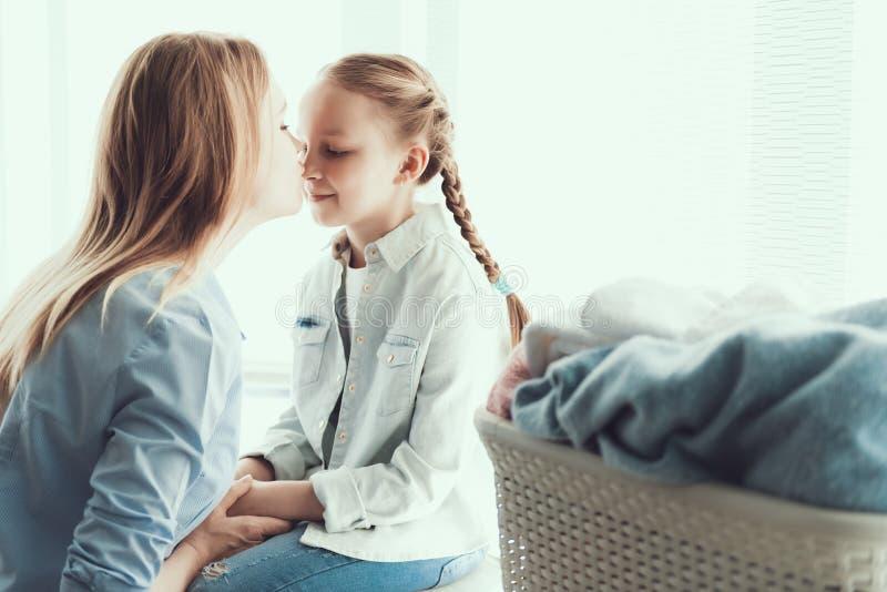 Jonge Gelukkige Moeder die Weinig Daugther in Neus kussen stock afbeeldingen