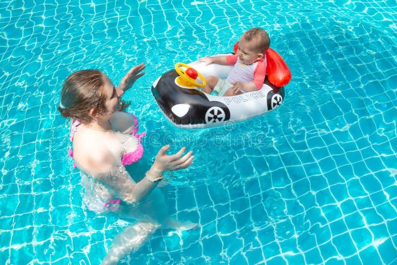 Jonge gelukkige moeder in een roze bikini die pret met een baby in de pool hebben Een blij klein kind zit in een opblaasbare boot royalty-vrije stock fotografie